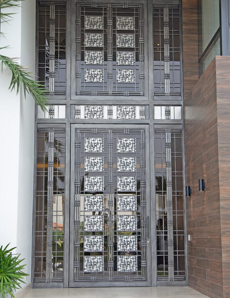 Oversized metal door composed of interlocking and overlapping squares which continuously flow throughout the front entrance