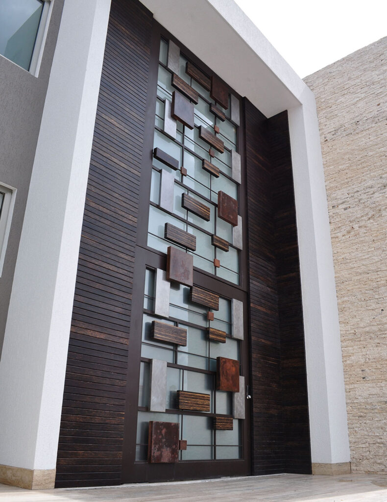 Oversized Wood Door Design, consists of small blocks of copper, aluminum, stainless steel, and bronze squares and rectangles that effortlessly blend in to create a modern design
